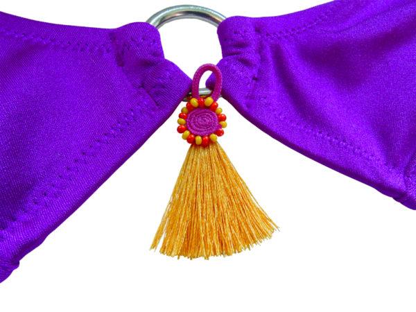 Perles, pompons, anneaux de métal, nœuds et fibres tressées